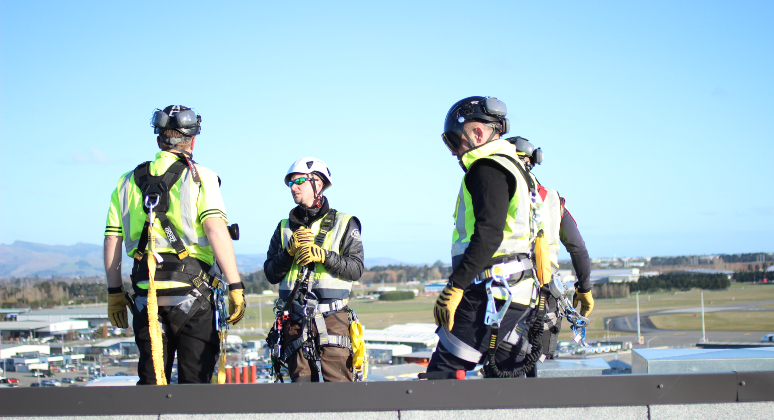 Four PBI Staff standing on a roof overlooking Christchurch with a full height safety solution.